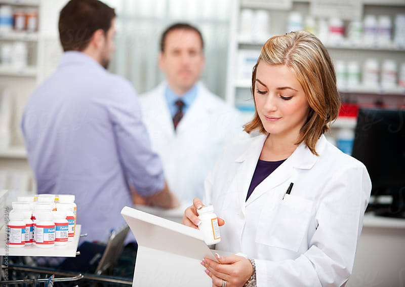 Pharmacy: Pharmacist Stocking Medicing on Shelves by Sean Locke for Stocksy United