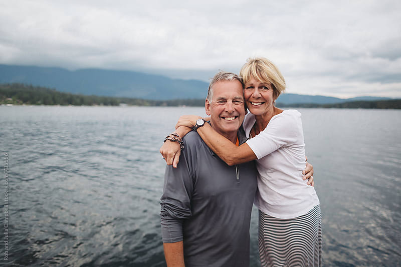 Mature couple looking at camera and smiling near lake by Rob and Julia Campbell for Stocksy United