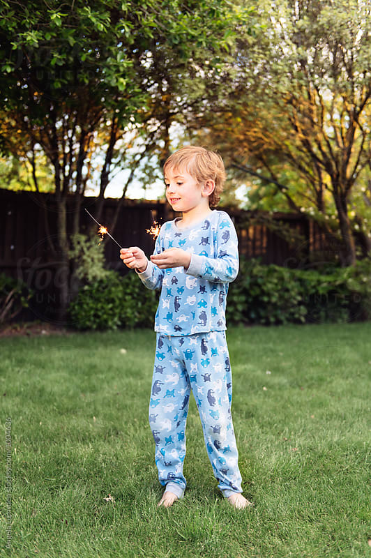 Happy child in pajamas with sparklers in the yard in the evening by Angela Lumsden for Stocksy United