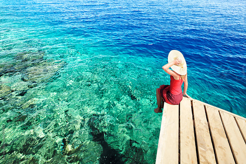 Young woman in sundress and sunhat sitting on pier looking at sea. by Ilya for Stocksy United