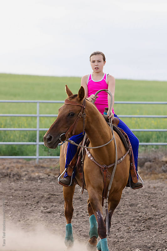 girl training horse in arena by Tana Teel for Stocksy United