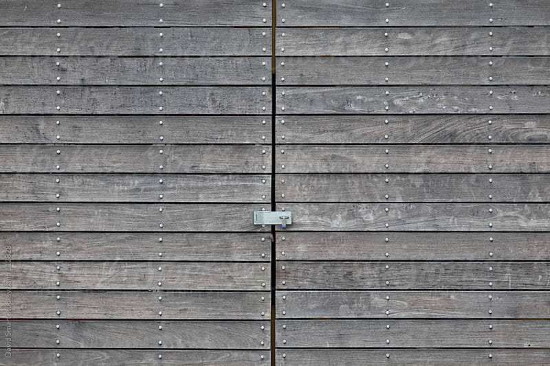 Weathered wood doors, with a padlock, on a storage building by David Smart for Stocksy United