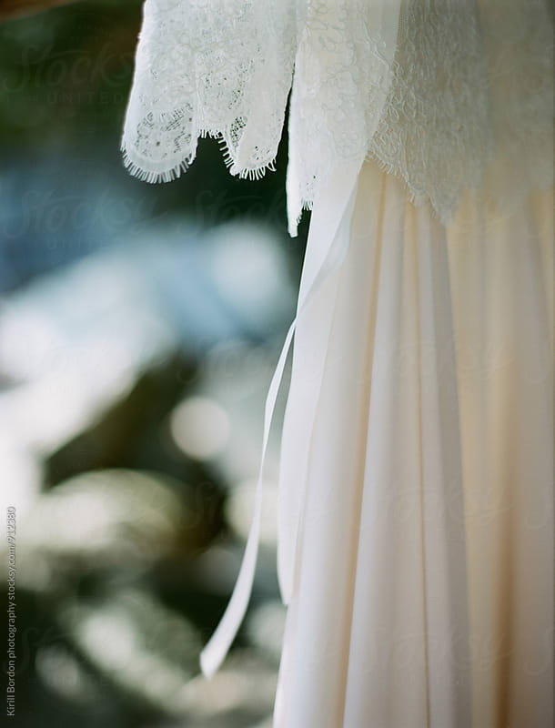 wedding dress hanging on a tree by Kirill Bordon photography for Stocksy United