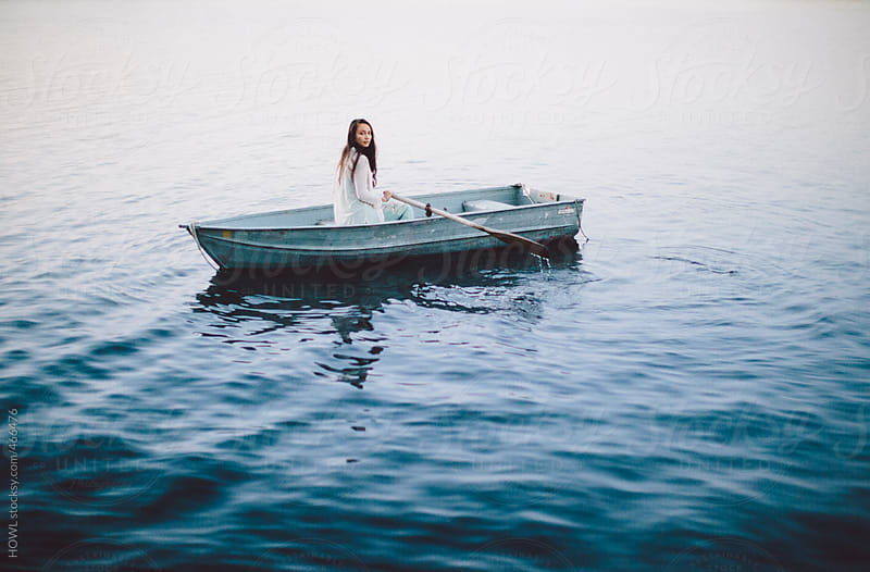 Lonely girl floats alone in a row boat on a foggy New England morning. by HOWL for Stocksy United