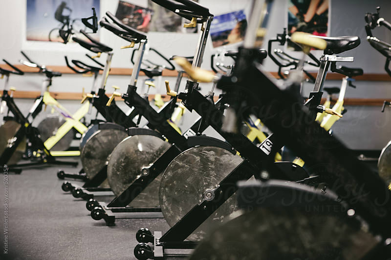 Many spin bikes in a group exercise room by Kristine Weilert for Stocksy United