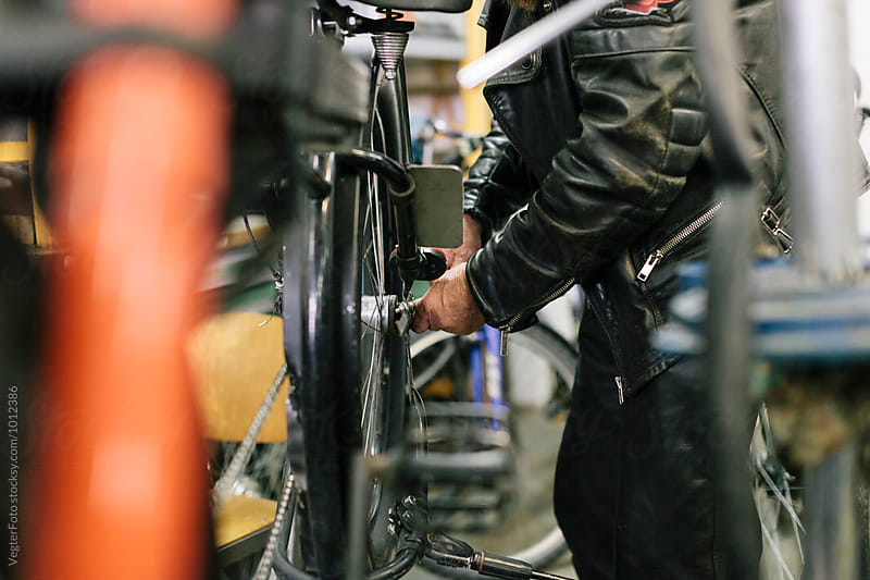Senior Bicycle Mechanic working by VegterFoto for Stocksy United