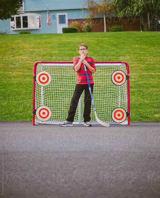 Portrait of Boy Playing Street Hockey by Raymond Forbes LLC for Stocksy United