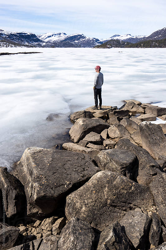 Man looking out over a frozen lake in Norway by Tristan Kwant for Stocksy United