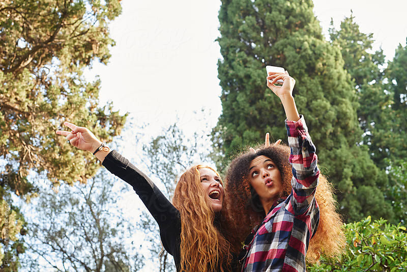 Two funny young women taking selfie in park by Guille Faingold for Stocksy United