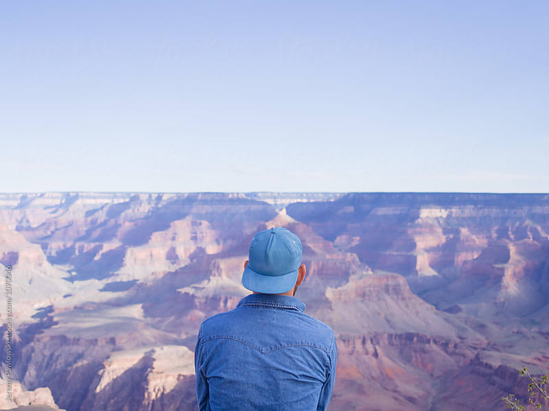 Man looking at Grand Canyon wearing denim with space for text above by Jeremy Pawlowski for Stocksy United