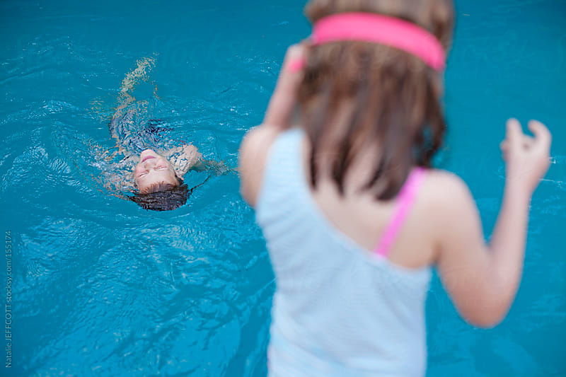 A young girl watches her brother swimming in a pool by Natalie JEFFCOTT for Stocksy United