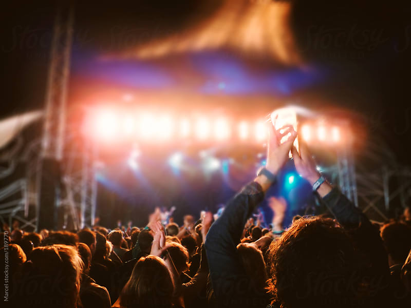 Cheering concert crowd at night by Marcel for Stocksy United