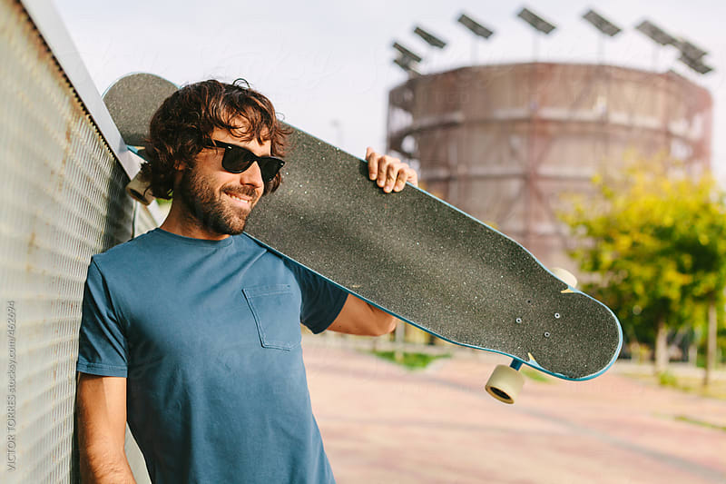 Young Man Posing with a Longboard by VICTOR TORRES for Stocksy United