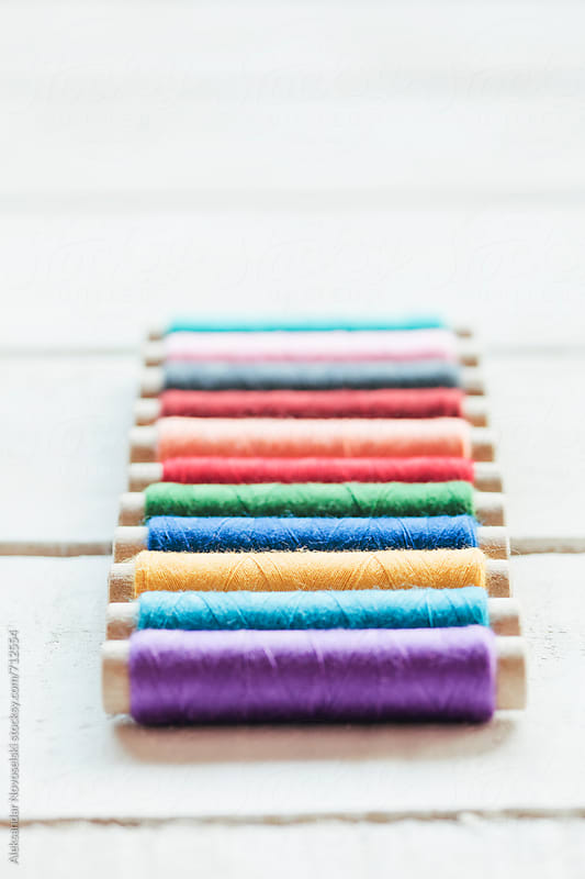 Detail shot of colorful threads on white wooden background  with very shalow depth of field by Aleksandar Novoselski for Stocksy United