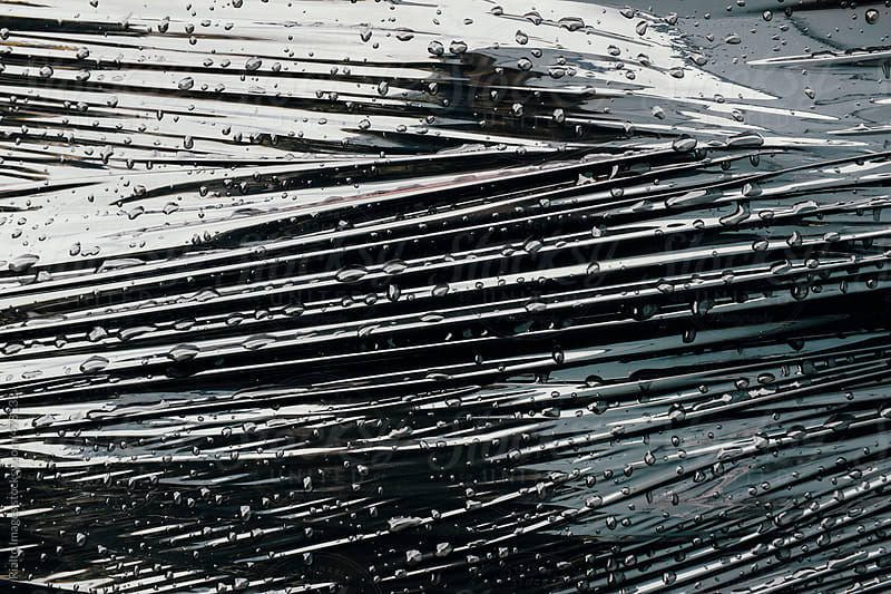 Close up of water drops on black plastic, wrapped around commercial fishing equipment by Paul Edmondson for Stocksy United