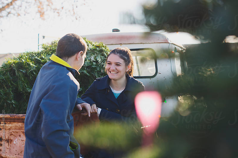 Young couple talk to each other at a Christmas tree lot by Tana Teel for Stocksy United