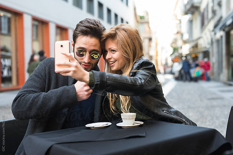 Couple relaxing at cafe in the city by Simone Becchetti for Stocksy United