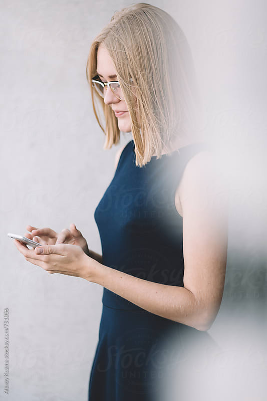 Happy businesswoman sending a message with smartphone on the street by Alexey Kuzma for Stocksy United