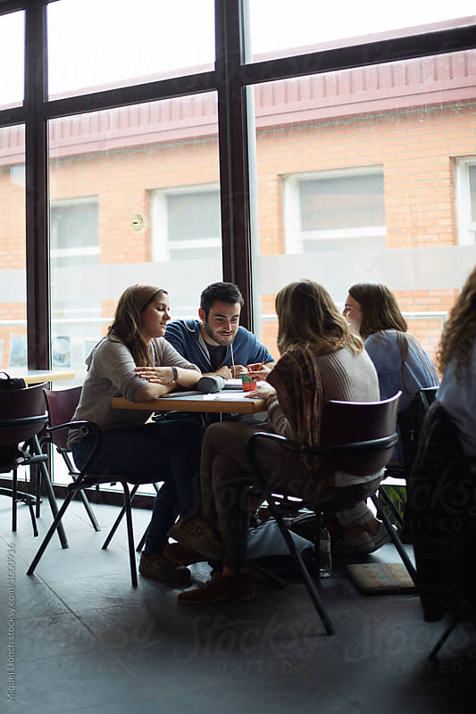 Teamwork with students at the university cafeteria by Miquel Llonch for Stocksy United