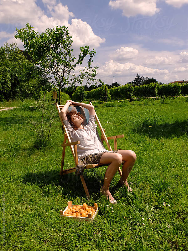A young woman sitting under the sun by Anna Malgina for Stocksy United