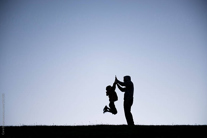 Evening silhouette of a boy jumping up to give his dad a high five by Cara Dolan for Stocksy United