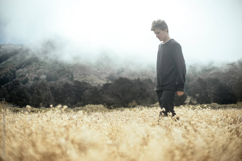 Travelling guy, wandering through the cornfields of Big Sur. by Christian McLeod Photography for Stocksy United