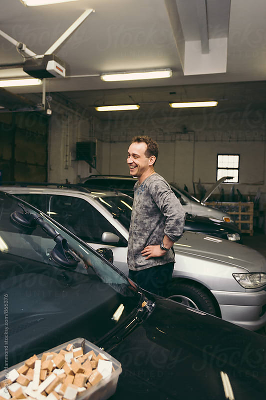 Man Laughing in Auto Repair Shop by Geoffrey Hammond for Stocksy United