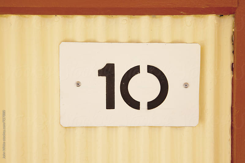 10 painted on a tin plate. by John White for Stocksy United