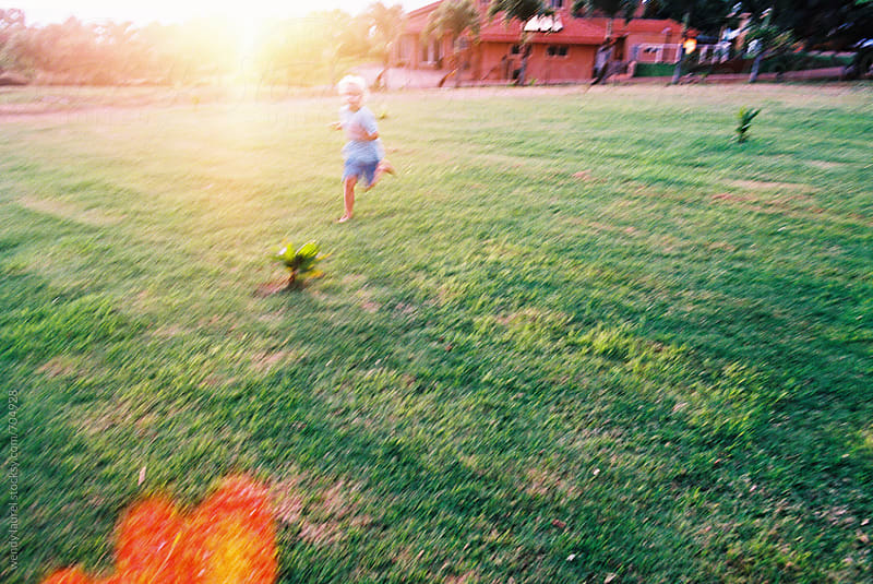 little boy running across sunlight lawn with flare by wendy laurel for Stocksy United