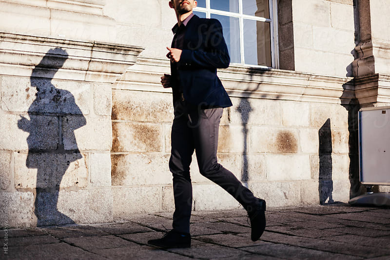 Business man walking through city by HEX. for Stocksy United