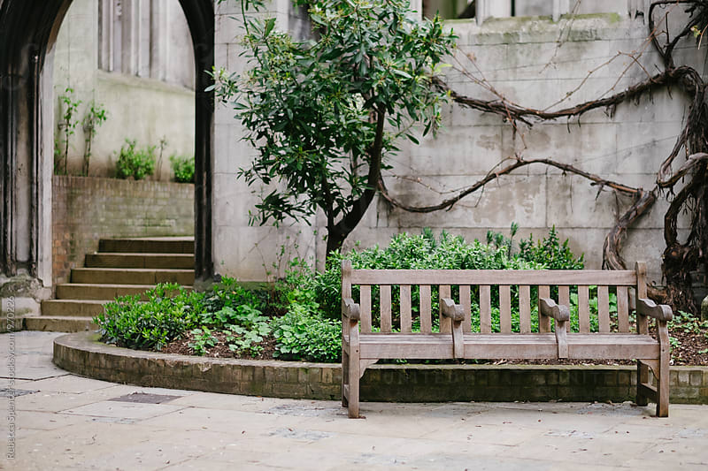 Three seater bench with stairs in background by Rebecca Spencer for Stocksy United
