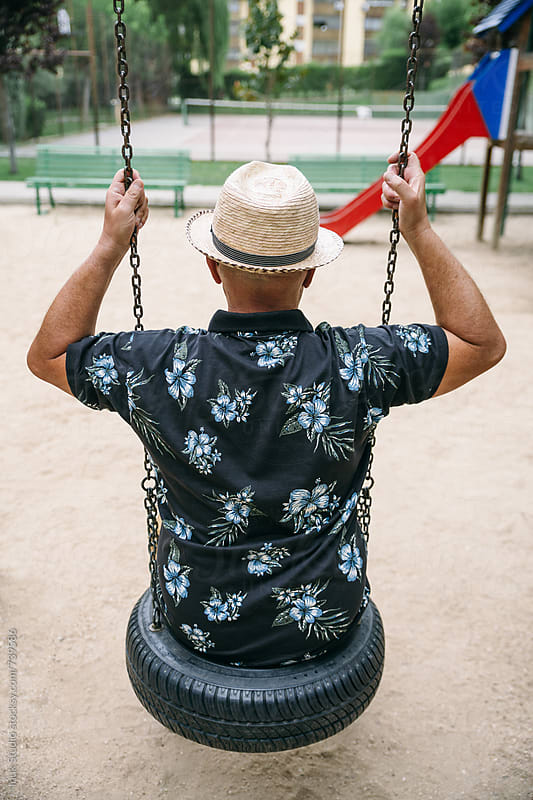 Back view of senior man playing on a swing in a children park. by Inuk Studio for Stocksy United