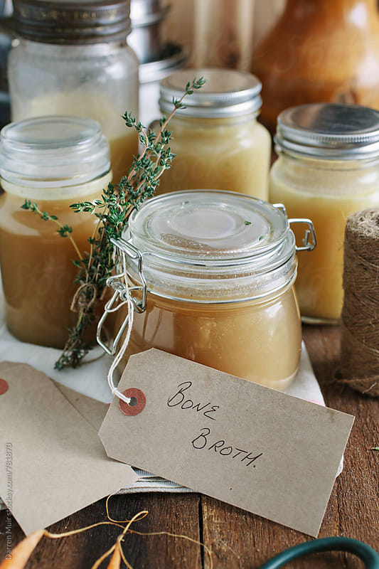 Bone broth: Various glass jars with different types of bone broth. by Darren Muir for Stocksy United