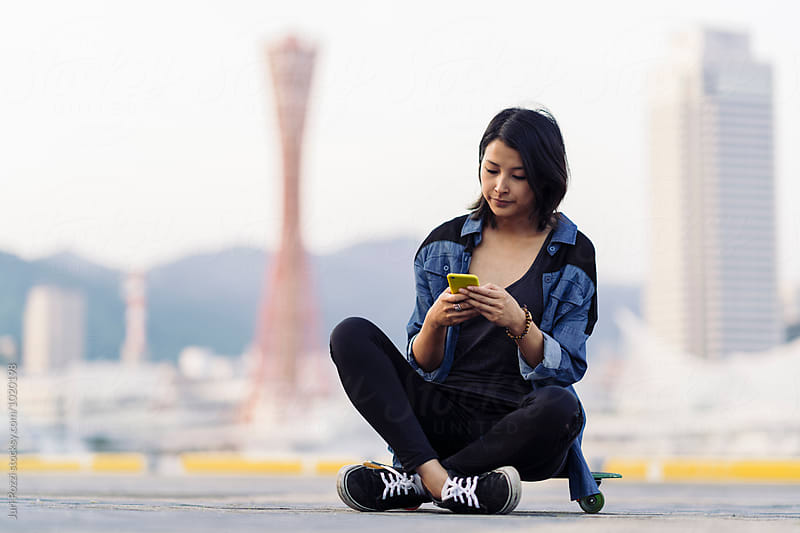 Young asian woman using a smartphone by Juri Pozzi for Stocksy United