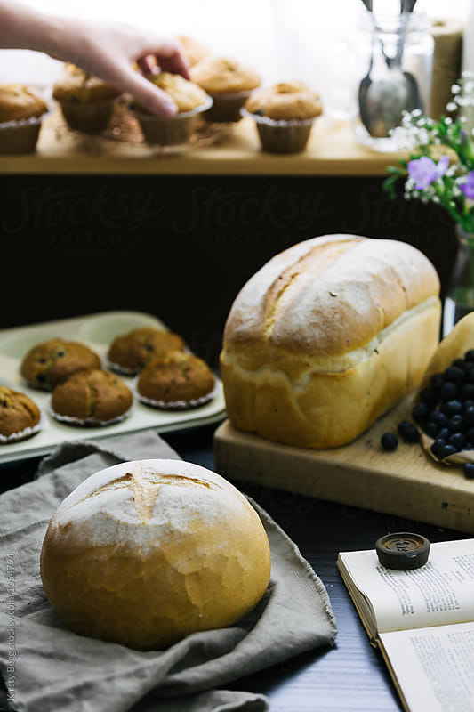 Fresh bread on table, woman places muffins to cool on window sill by Kirsty Begg for Stocksy United