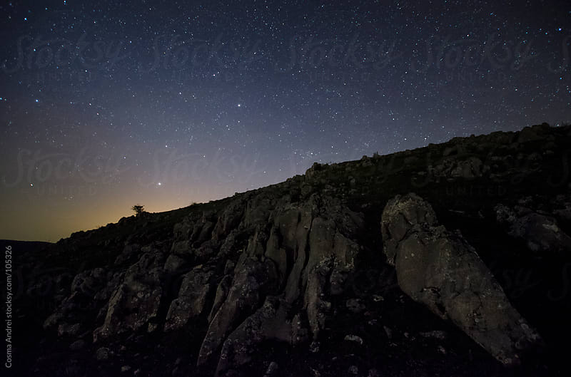 Twilight with starry sky over mountain cliffs by Cosma Andrei for Stocksy United