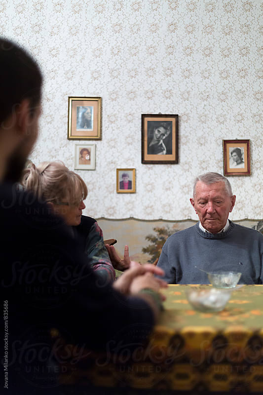 Young man and adult woman sitting and talking with a senior man in the living room  by Jovana Milanko for Stocksy United