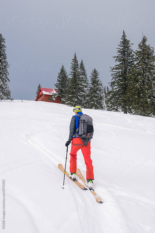 Skier going uphill on his skis, cross-country skiing by RG&B Images for Stocksy United
