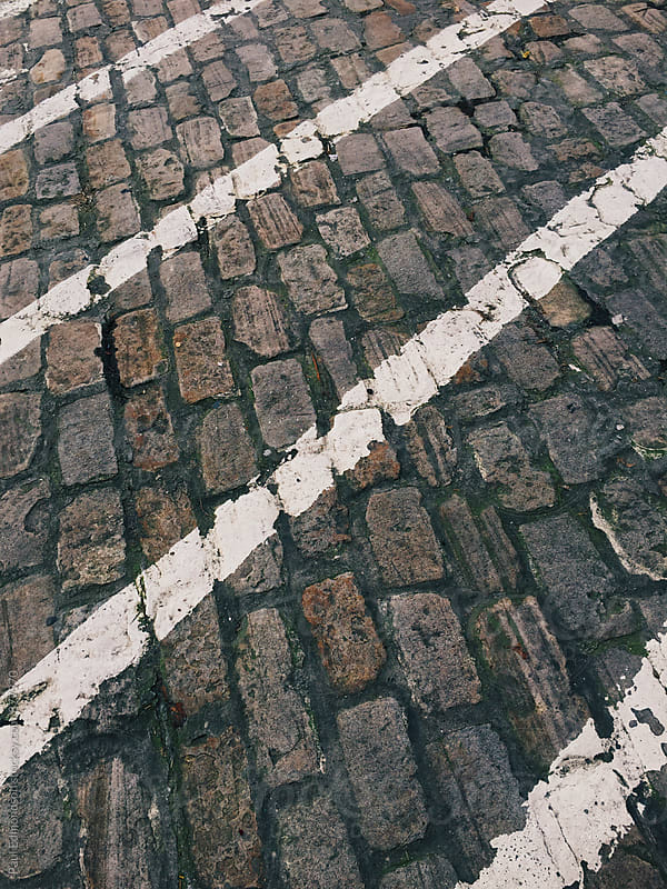 Painted white lines on cobblestone street by Paul Edmondson for Stocksy United