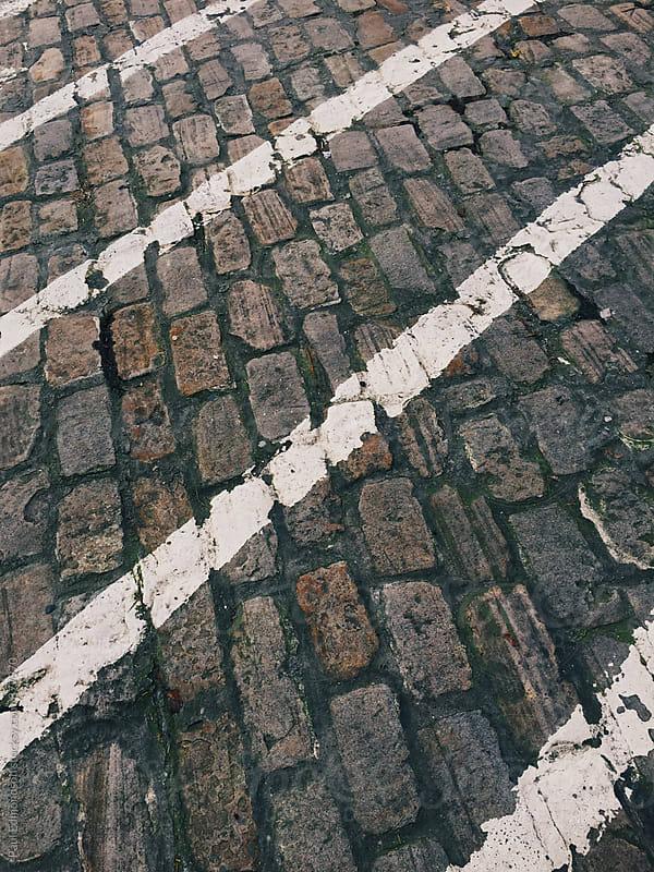 Painted white lines on cobblestone street by Paul Edmondson for Stocksy United