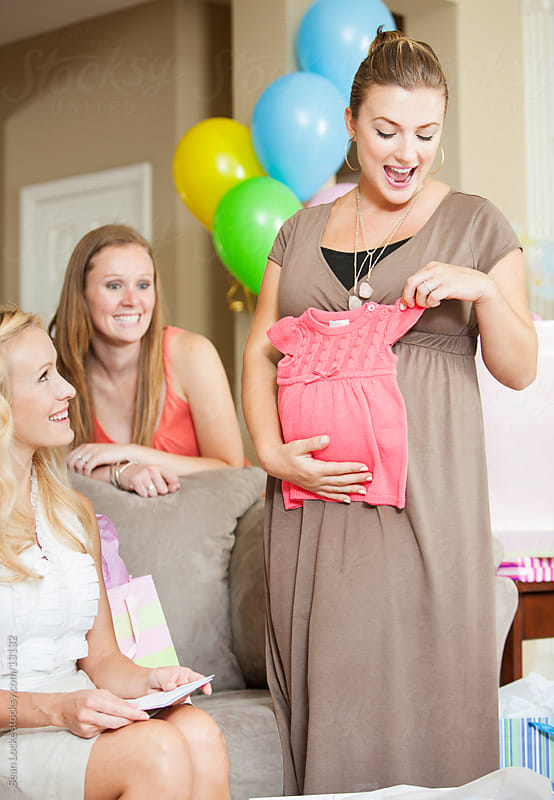 Baby Shower: Holding Baby Dress Over Belly by Sean Locke for Stocksy United