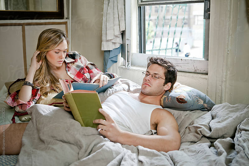 Young Couple Reading in Bed by Joselito Briones for Stocksy United