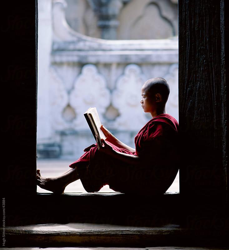 Novice Monk reading in doorway. Myanmar. by Hugh Sitton for Stocksy United