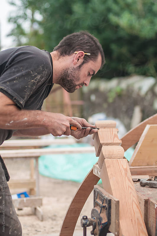 A joiner working on shaping a piece of wood by Andy Campbell for Stocksy United
