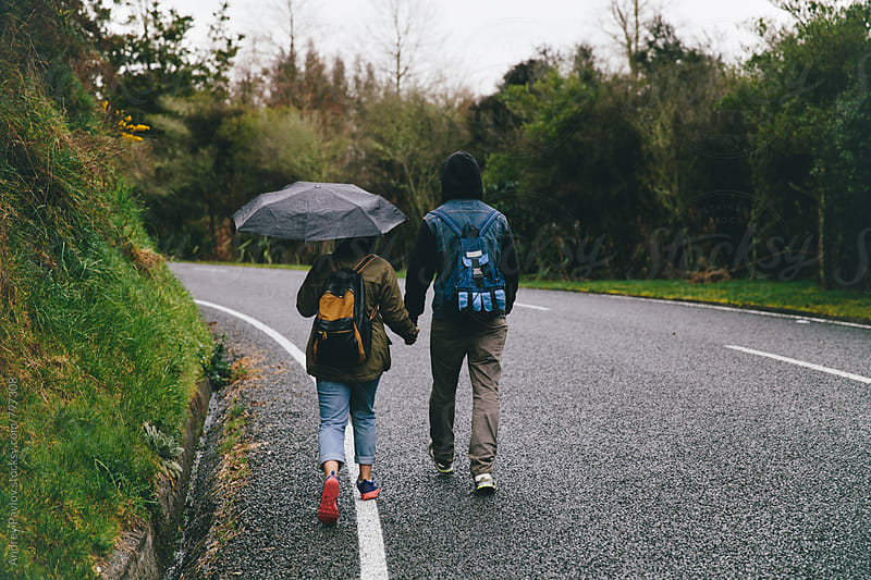 Couple of backpackers with umbrella walking along the road by Andrey Pavlov for Stocksy United