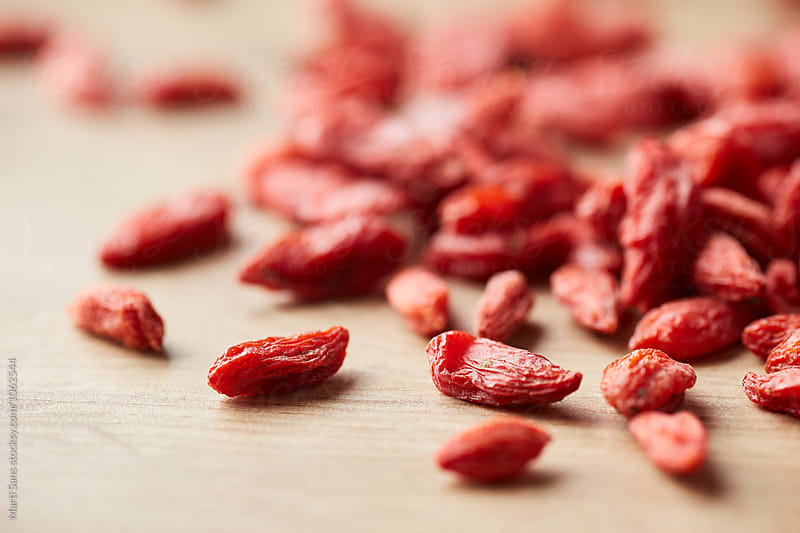 Scattered goji berries on table by Martí Sans for Stocksy United