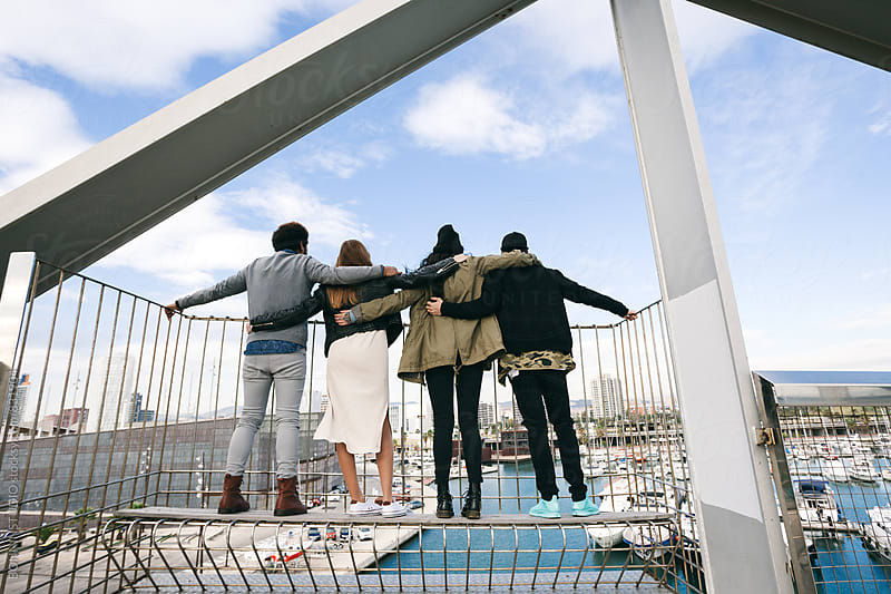 Back view of group of friends embraced looking seaport from bridge. by BONNINSTUDIO for Stocksy United