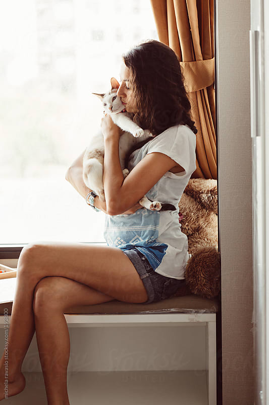 Young woman hugging her cat by michela ravasio for Stocksy United