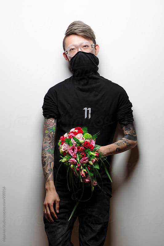 Portrait of man with tattoo holding a bunch of flower by MaaHoo Studio for Stocksy United