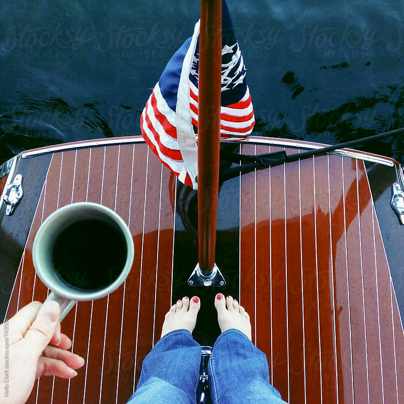 A women enjoys coffee on the back of a wooden boat by Holly Clark for Stocksy United